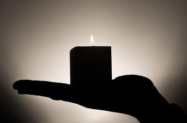 Ruka drží sviečku, siluety