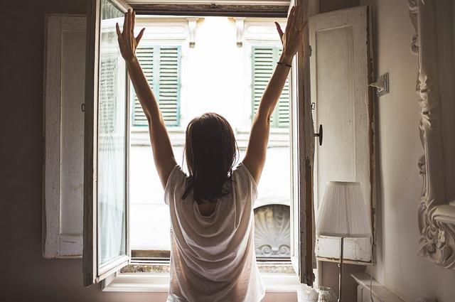 Žena v bielom tričku sa naťahuje pri otvorenom okne