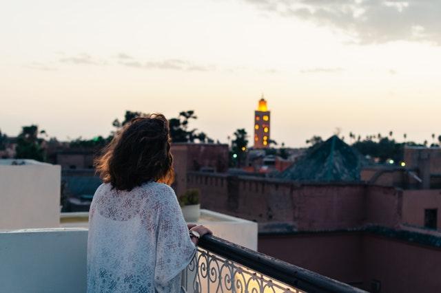 Žena v bielych čipkovaných šatách stojí pri zábradlí na balkóne počas východu slnka