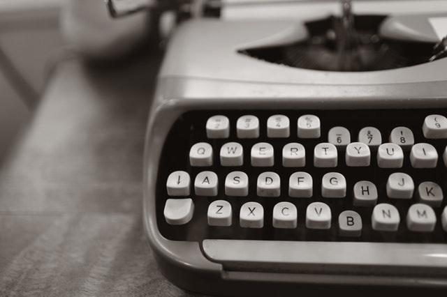 Biely písací stroj položený na stole.jpg