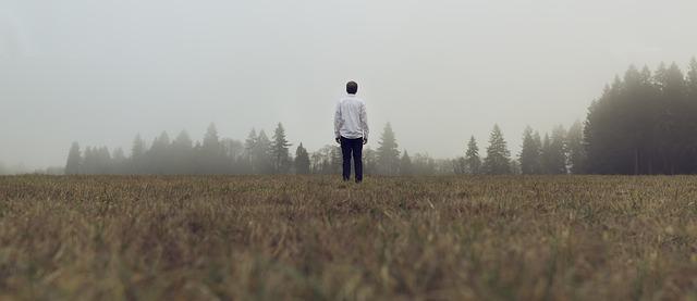 Muž v bielej košeli stojí uprostred poľa a pozerá do diaľky.jpg